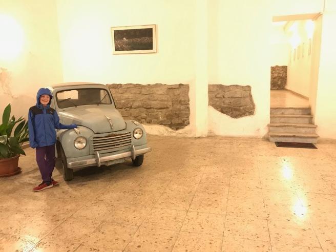 A boy standing next to a small, blue car inside a building lobby