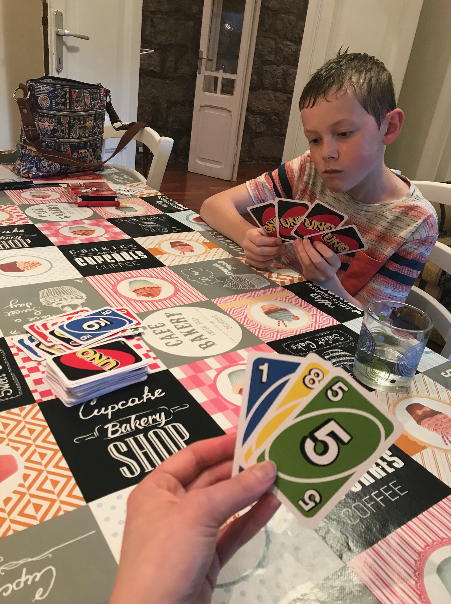 A boy playing Uno at a kitchen table