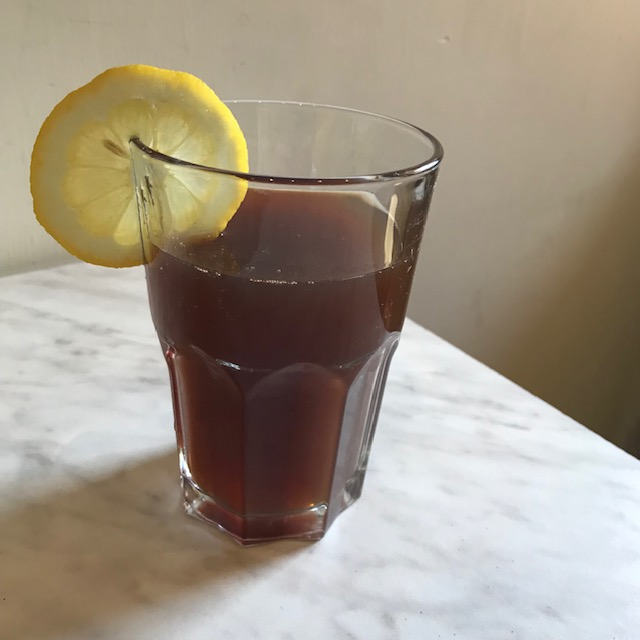 A glass of ice tea with lemon