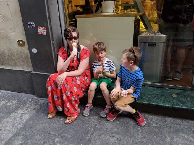 A woman in a long dress eats gelato on a sidewalk with two children